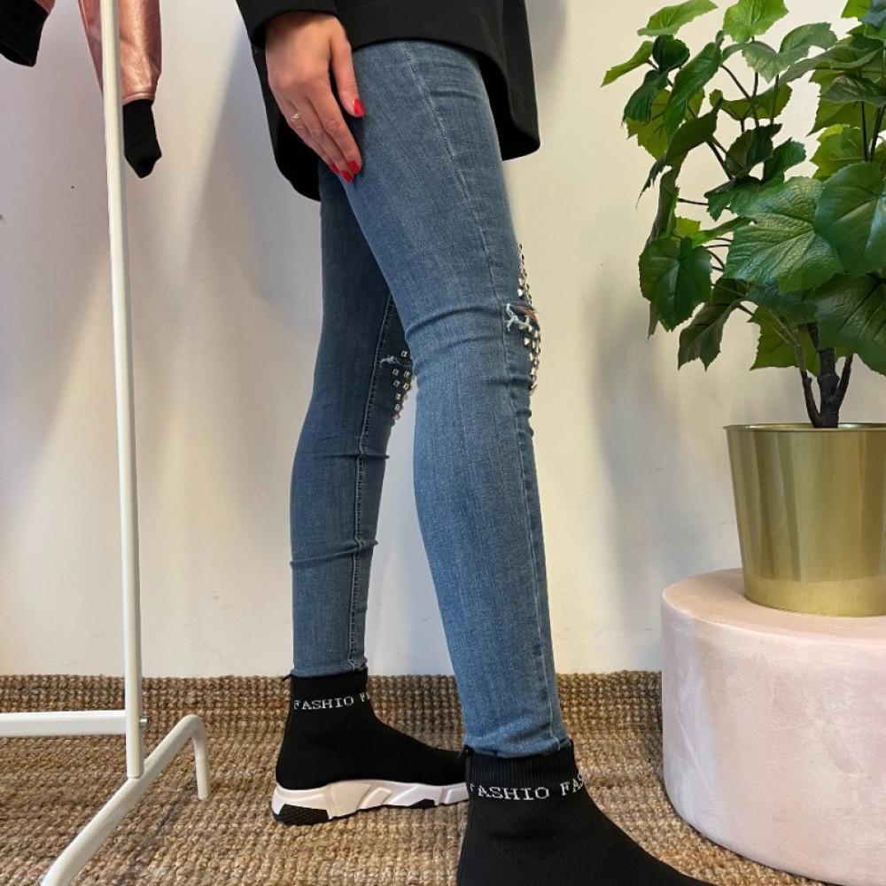 Džinsa bikses ar plēsumu ceļa daļā